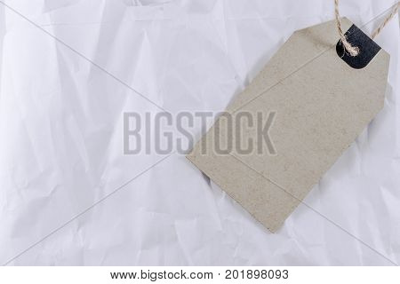 Blank paper label or cloth tag on wrinkled white paper texture or background
