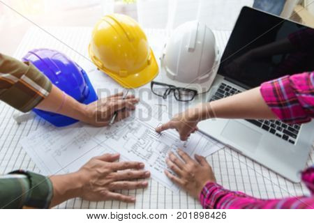 Construction officer is picking up protection helmet in officeWorkers and manager in safety helmets working with documents at factory
