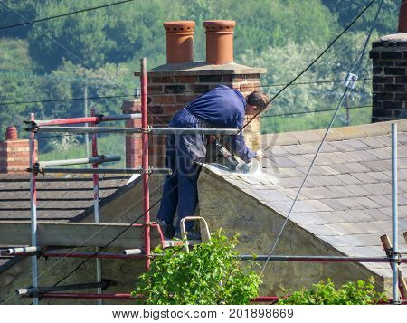WREXHAM UK - May 25 2017: Roofer repairing flashing on chimney stack on a slate roof of a domestic house. Standing on scaffolding. Close up high angle point of view. Countryside background.