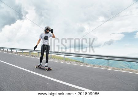 A young guy in a full-face helmet rides a country road at high speed in the rain amid thunderstorm clouds