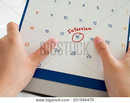 Woman hand hold white calendar with red interview word marked on calendar. Important interview meeting with potential new employer.
