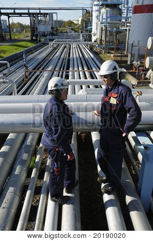 two engineers standing on pipelines inside an oil and gas refinery