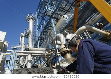engineer working on pumps, oil and gas refinery in background