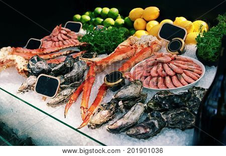 Raw crab legs, shrimps and oysters on ice in seafood restaurant, toned image