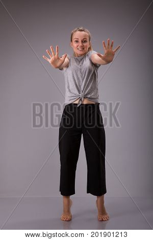 Prohibition symbol. Smyling female shows stop sign talk to hand gesture. Full height portrait of young girl over gray background