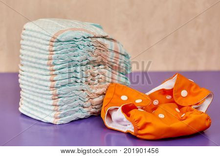 Stack of disposable diapers or nappies on purple background and reusable one