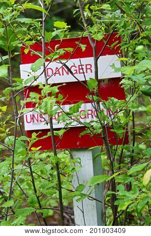 A Danger, Unstable Ground Sign Obscured By Trees