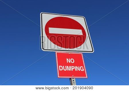 No Entry Or Dumping Sign Against Blue Sky