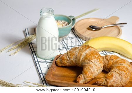 Breakfast with Croissant and Muesli and banana and fresh milk give vitamins minerals carbohydrates fats oils protein.