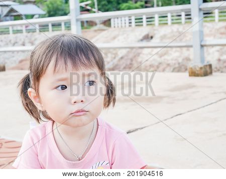 portrait of little girl scowling face playing in the park and soft focus , asian baby girl