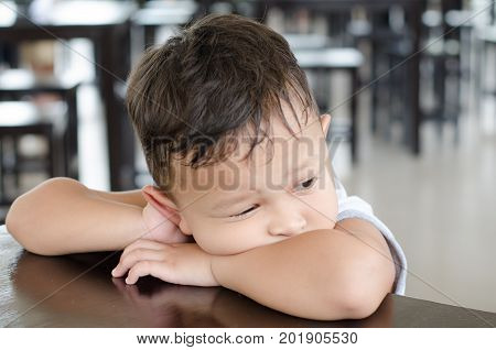 Boy about 4-5 years old seat alone in library with very sadness and thinking something and same like waiting some one.