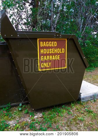 A bagged household garbage only dumpster in campground.