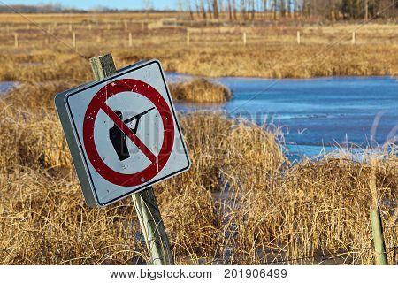Bullet Ridden Sign Along A Wildlife Pathway