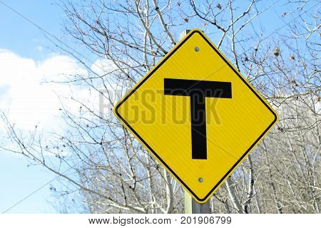 A warning T crossing road sign against trees