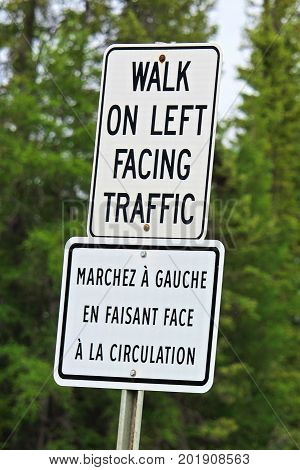 A Walk On Left Facing Traffic Sign In Both English And French