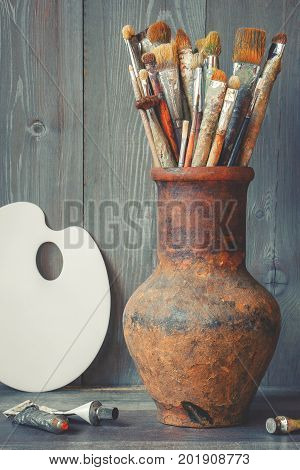 Brushes of the artist in an old clay jug tubes with paint and a white palette stand against the background of a wooden wall in the artist's studio