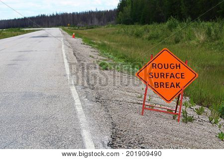 An Orange Rough Surface Break Sign With A Road Into The Distance