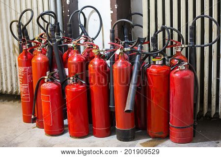 Many red fire extinguishers on the ground. Foam Carbon dioxide Powder and Water.
