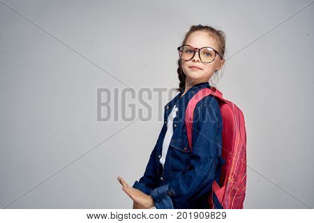 little girl with glasses with a backpack, empty space for copying.