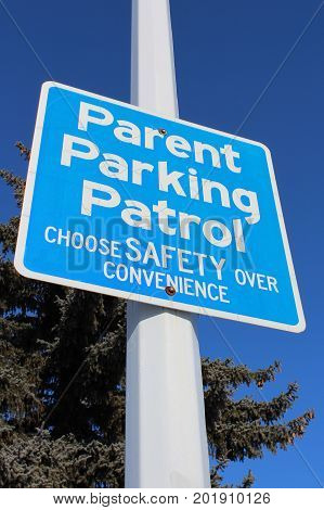Parent Parking Patrol Sign Against Tree And Blue Sky