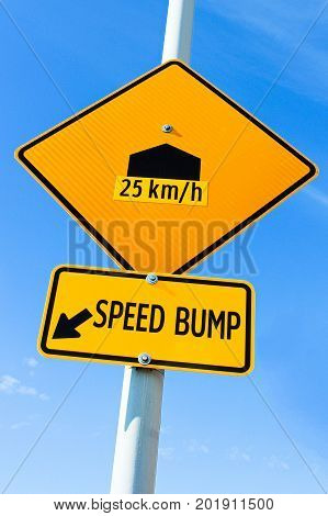 A speed bump sign with speed recommendation.