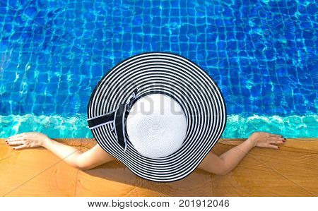 Women big hat lifestyle relaxing near luxury swimming pool sunbath summer day at the beach resort in the hotel. Summer Concept