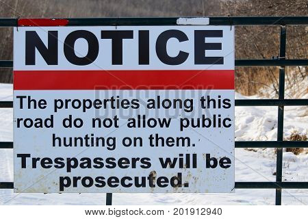 No Trespassing Or Hunting Sign On A Gate