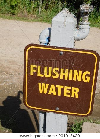 A flushable water station sign at a campground.