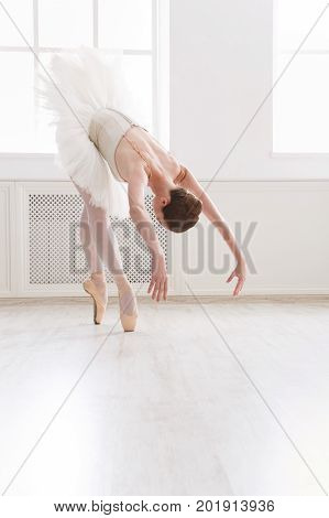 Beautiful graceful ballerina practice in tutu skirt near large window in white light hall. Classical ballet dancer at dance class, side view, copy spce
