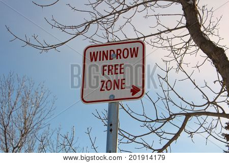 Windrow Free Zone Sign Against Blue Sky