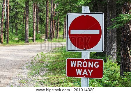 A Do Not Enter, Wrong Way Sign Beside A Gravel Road