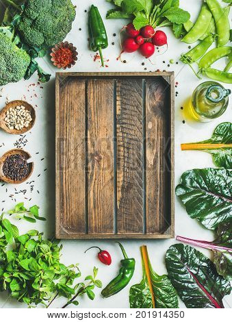 Fresh raw greens, unprocessed vegetables and grains over light grey marble kitchen countertop, wooden box in center, top view, copy space. Clean eating, healthy, vegan, detox, dieting food concept