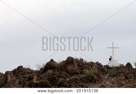 TUCSON, ARIZONA - FEBRUARY 12, 2012. A girl is sitting near the cross in Mission San Xavier del Bac near Tucson, Arizona.