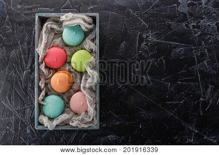Classic French multicolored macaroon cookies in a wooden box on a black concrete background