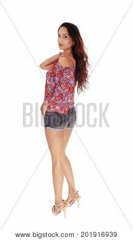 A slim young woman standing in shorts and colorful blouse from the back looking over her shoulder isolated for white background