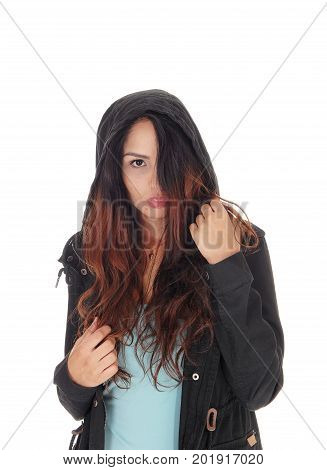 A young woman standing in a turquoise t-shirt and black jacket with a hoody covering halve her face with her hair over white background