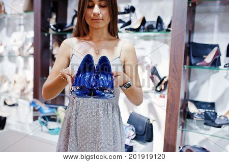 Portrait Of A Woman Holding High-heeled Shoes In A Shoe Shop.