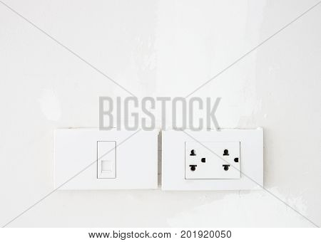 Electrical switch and telephone socket on the white wall in the living roomcopy space.