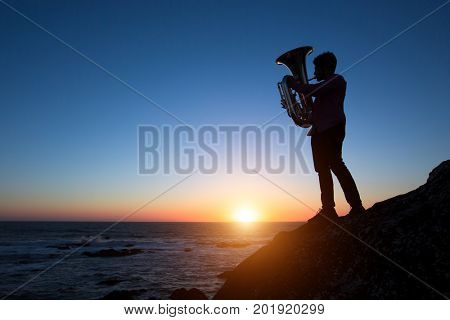 Silhouette of musician play Tuba on sea shore at beautiful sunset .