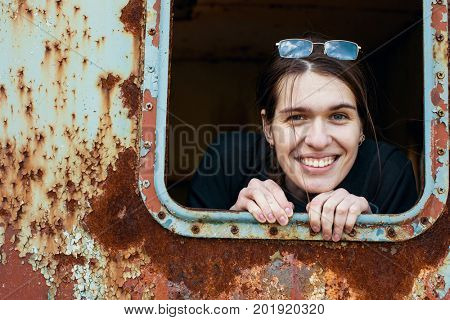Attractive young woman looking out of the window metal caboose.