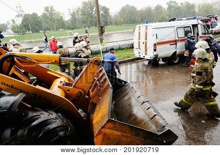 Orel Russia August 29 2017: Collapse of old apartment house. Road grader and ambulance car at muddy road in catastrophe site at rainy day