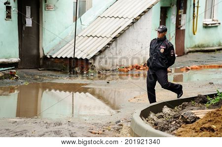 Orel Russia August 29 2017: Collapse of old apartment house. Policeman runs near big puddle in dirty abandoned yard