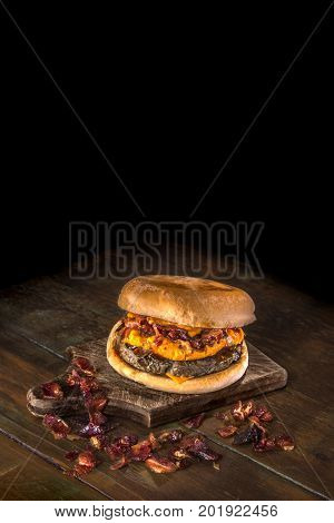 Delicious hamburger with fried and crunchy bacon, melted cheddar and barbecue sauce on a dark wood background