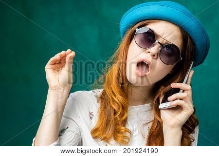 Hand gesture,Woman speaking with smartphone and shows keep silence with hand.Girl get tired to speak on mobile phone,don`t want listen.Hand shows stop blah blah symbol of speaking mouth