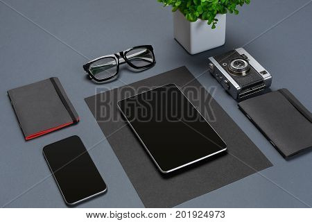 A set of black office accessories, glasses, green flower and smart on gray background. Flat lay. Still life. Mock-up
