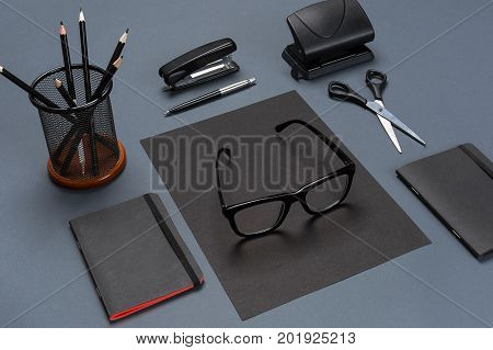 A set of black office accessories, glasses on gray background. Flat lay. Still life. Mock-up