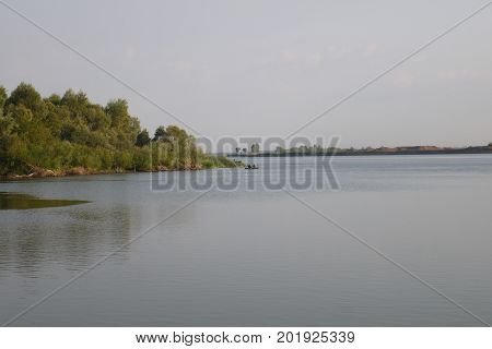 The water smooth surface of the lake bordered with the coastline