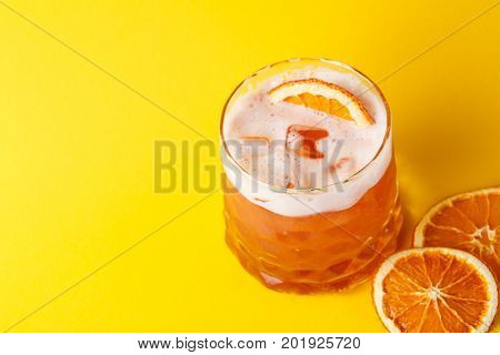 Cocktail on juicy orange background. Citrus alcohol beverage with tequila, blood orange juice and ginger beer, served with citrons and ice, copy space