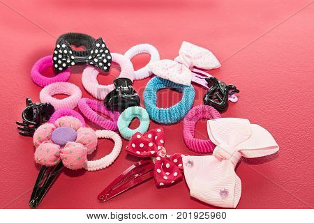 Still life with buckles of flower shapes and bows elastic bands and hair clips. Red background.