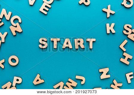 Word Start on blue background, in wooden letters frame. New beginning, startup, challenge concept